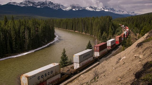A Canadian Pacific Railway freight train makes its way westward along the Bow River