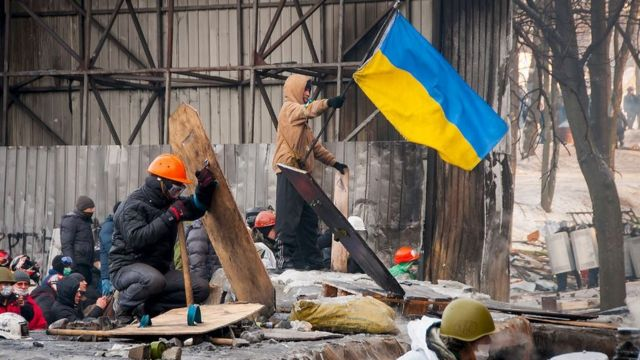 Протестувальники зі щитами і прапорами на барикадах