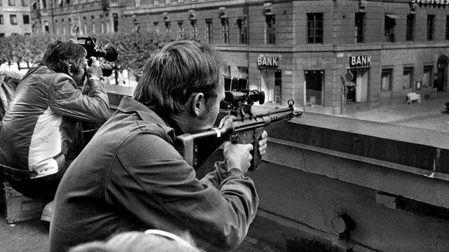 Policial armado e jornalista com câmera