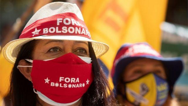 Mulher com máscara e chapéu que estampam símbolo do PT e frase 'Fora Bolsonaro'