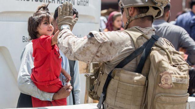 سرباز آمریکایی و کودک در فرودگاه کابل