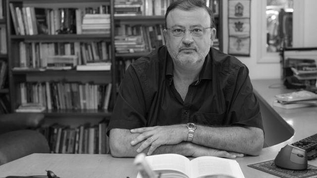 Dunker sentado em mesa, com livro na frente e rodeado por estantes de livro