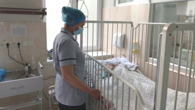 Enfermeira ao lado de criança com catapora