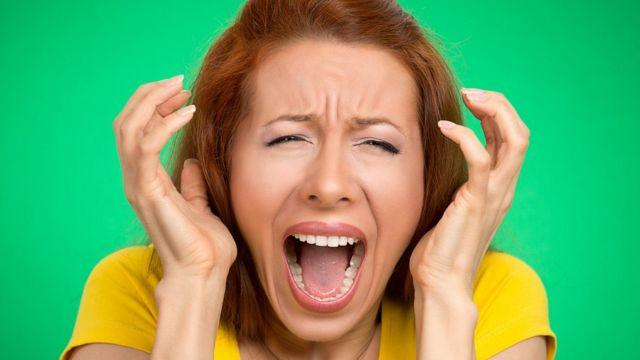 Mujer desesperada tapándose los oídos