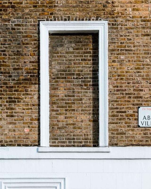 Brick wall with a single blocked window, on Abingdon Villas, London