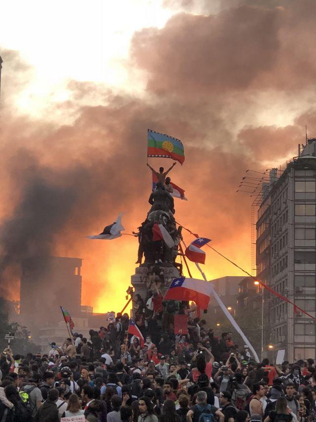 Manifestantes sobre estátua militar no centro do Chile