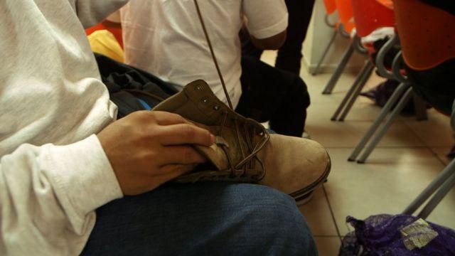 Un retornado atándose el zapato.