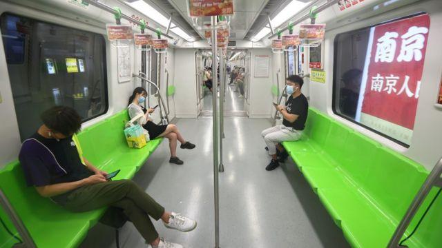 中国江苏南京地铁上乘客戴着口罩出行(中新社图片27/7/2021)