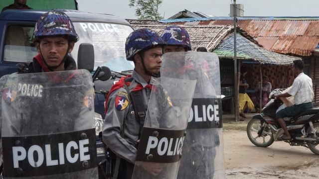 three police officers with helmets and shields looking wary