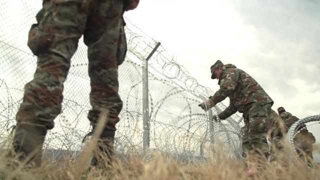 Macedonian troops build a wire fence on Macedonia's border with Greece