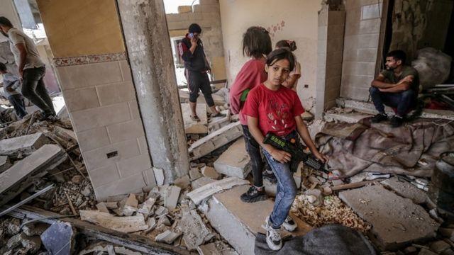 Chicas palestinas de pie entre los escombros de una casa