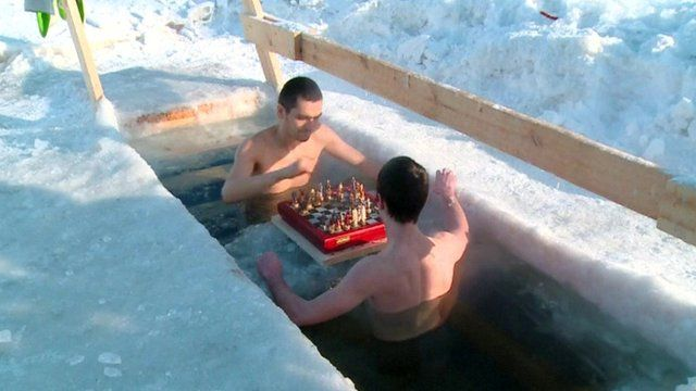 Two contestants play chess in a freezing pool.