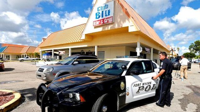 A Fort Myers police officer is seen at a parking lot of Club Blu after a shooting in Fort Myers