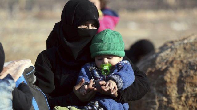 امرأة سورية تجلس مع طفلها
