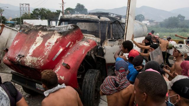 Personas atacando un vehículo