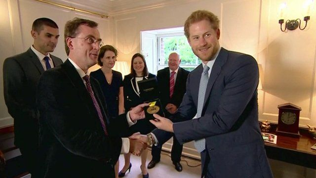 Prince Harry presenting an Invictus Games gold medal won by a US soldier, to UK medical staff