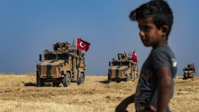Niño en la frontera de Turquía y Siria con tanques militares en el fondo.