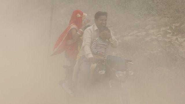 Pai, mãe e filhos em moto em meio a nuvem de poeira