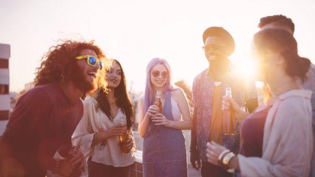 Grupo de amigos dando risada e bebendo ao pôr do sol