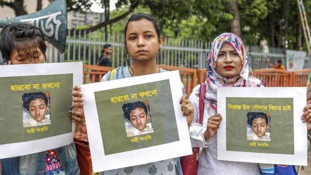 ผู้หญิงถือแผ่นป้ายที่มีภาพของ นูสรัต จาฮัน ราฟี นักเรียนหญิง ที่การประท้วงในกรุงธากา