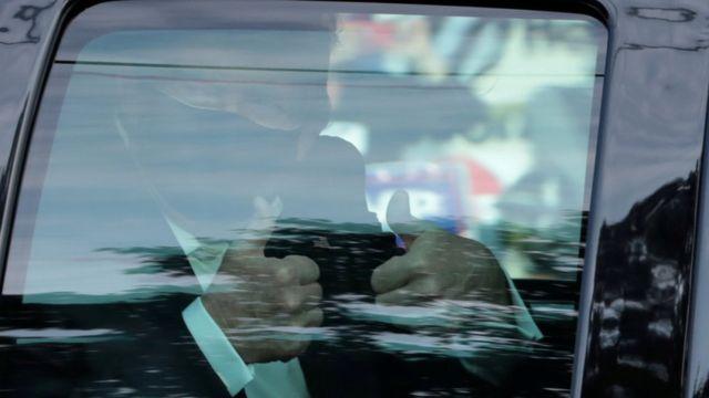特朗普周日坐车现身,向支持者举起姆指,随即返回医院。