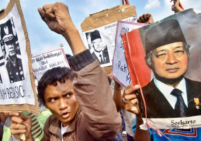 Indonesian students hold a rally as they protest against the decision to drop the graft case against former dictator Suharto (pictured R), in front of the Presidential Palace in Jakarta, 18 May 2006. A graft case against Suharto, who is accused of embezzling billions of dollars of state assets during his 32-year rule, has been dropped due to his deteriorating health