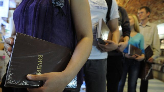 Люди с Библиями в очереди в книжном магазине