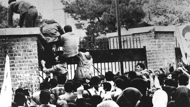 İranlı öğrenciler ABD Büyükelçiliğinin duvarınan tırmanırken, 4 Kasım 1979