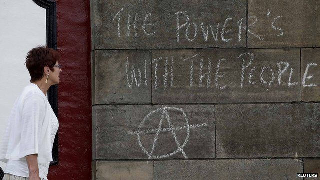 """A woman walking past a message drawn in chalk during an anti-fracking demo which says: """"The Power's with the People!"""""""