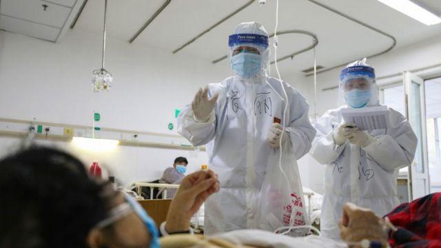 武汉金银潭医院的医护人员正在检查一名新冠肺炎患者的身体状况。