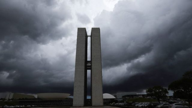Prédios do Congresso Nacional sob nuvens pesadas em Brasília