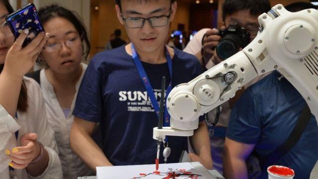 Jovens observam robô pintando durante a abertura do 3º World Intelligence Congress em Tianjin, na China.