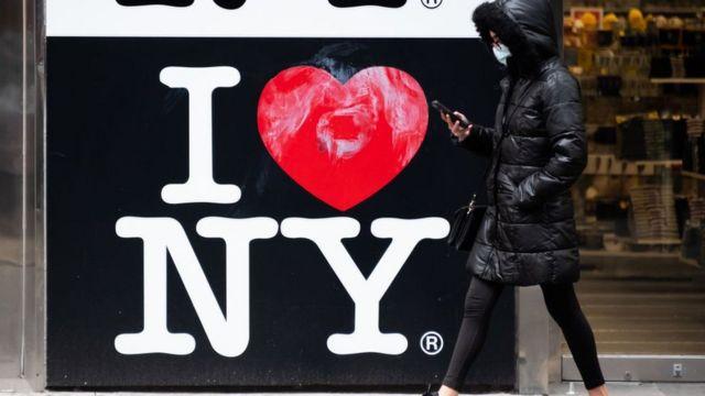 """Eine Frau, die an einem Schild vorbeikommt """"Ich liebe New York"""""""
