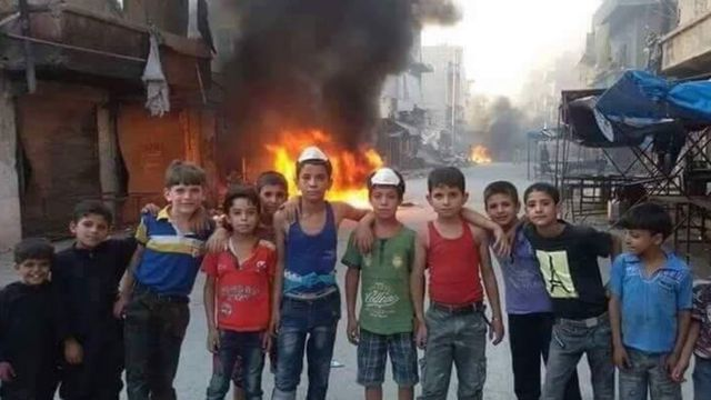 Un grupo de niños en Alepo junto a una pila de ruedas ardiendo.