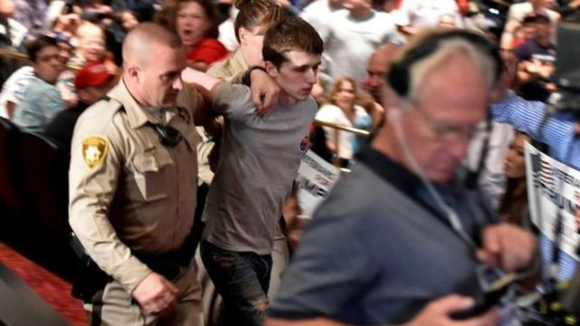 Police led the suspect away at Saturday's rally