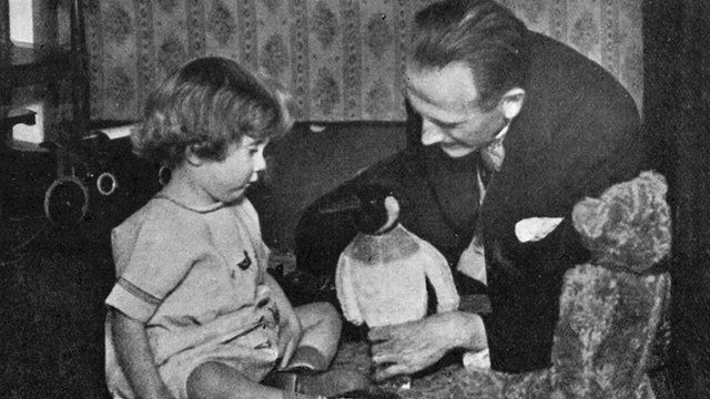 A. A. Milne and Christopher Robin Milne playing with a toy penguin