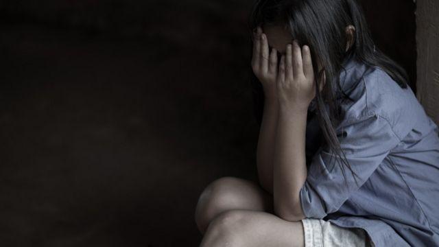 Una niña sentada se cubre el rostro con las manos en señal de desesperación