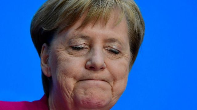 German Chancellor Angela Merkel closes her eyes as she gives a press conference on 29 October