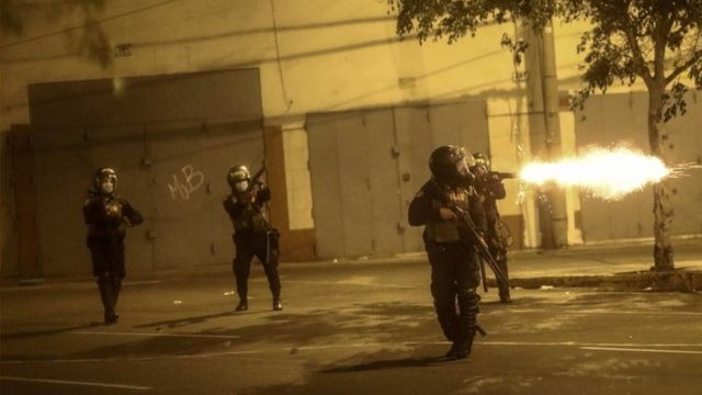Policías disparando gases lacrimógenos contra los manifestantes.