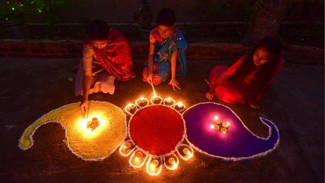 भारतको आसाममा रङ्गोली वरिपरि दियो बाल्दै किशोरीहरू