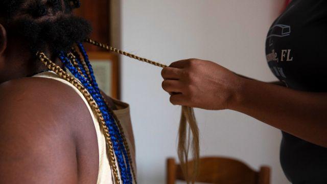 Une Nigériane tresse les cheveux d'une autre femme dans un refuge en Sicile après avoir échappé à des réseaux de trafiquants