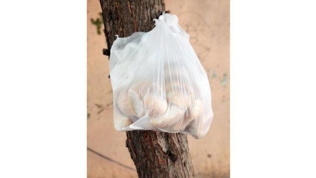 أكياس بلاستيكية معلقة على الأسوار القديمة تحوي خبزا قديما لمن يحتاجه