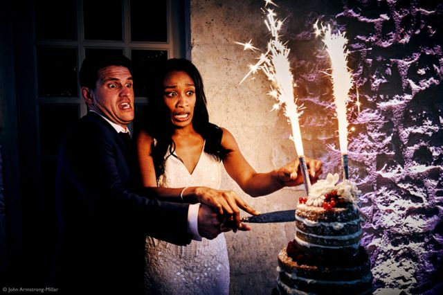 A man and woman cutting a wedding cake that has sparklers on top