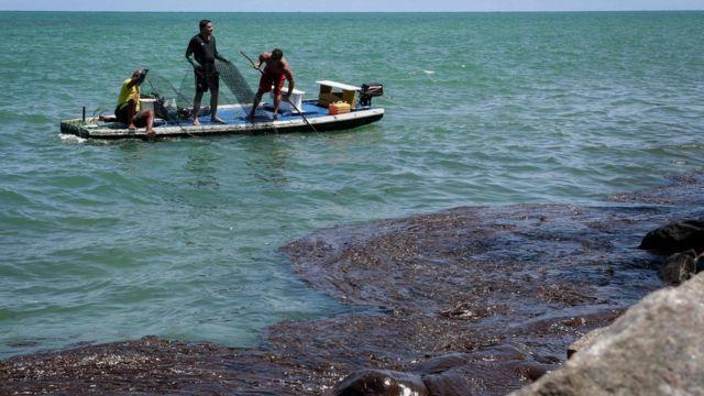 Jangada com três homens segurando rede de pescar e mar com manchas de óleo, no litoral do Pernambuco