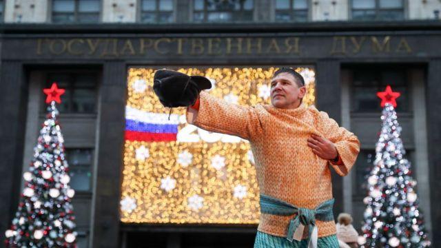 Артист в национальном костюме на фоне Госдумы и елок