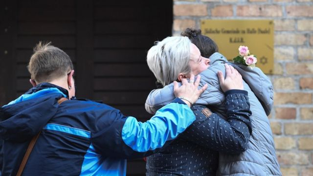 Mourners hug in front of the synagogue in Halle, 10 October