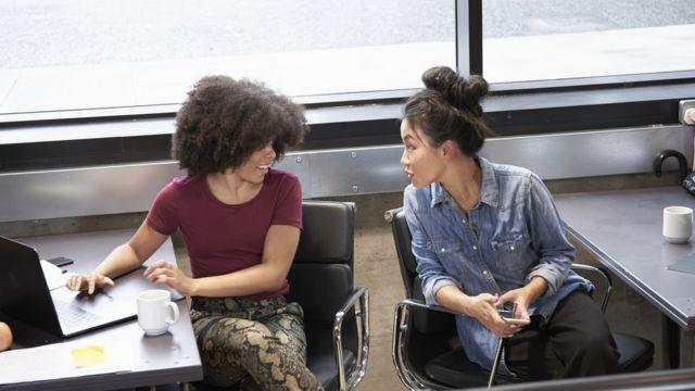 Dos mujeres conversando una con la otra, cada una su escritorio.