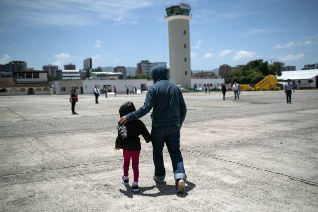 Un padre camina junto a su hija en el aeropuerto de Brownsville, TX, rumbo a un vuelo de deportación.