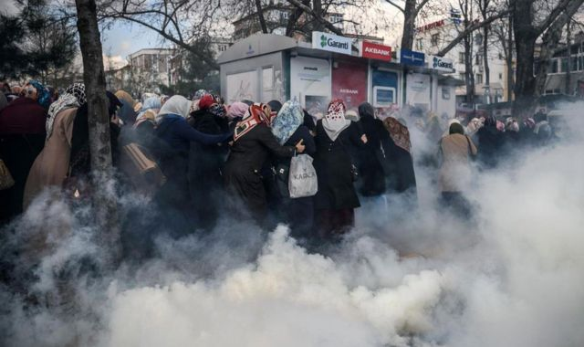 Mujeres corriendo entre gases lacrimógenos
