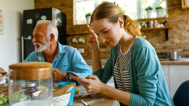 Un grand-père et une petite-fille se partagent le petit déjeuner sur la table de la cuisine.
